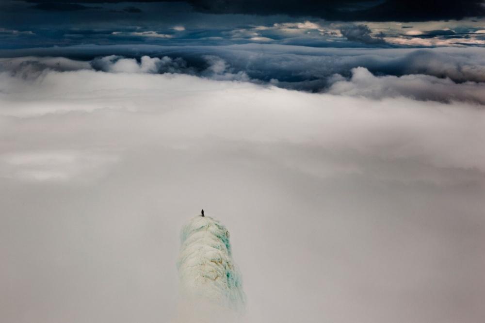 یک کوهنورد روی نوک کوهی در کشور ایسلند ایستاده است